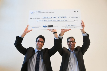 Panasci winners Parham Rohani and S. Bruce Kohrn holding up a big check that reflects their winnings for taking first place.