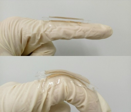 A prototype of the triboelectric nanogenerator lying on two gloved fingers -- prototype is flat on one finger and bent over a knuckle of the other finger.