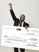 Ogechi Ogoke celebrates his win with a fist in the air while holding his ceremonial check for $25,000.