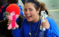 A photo of a female student showing off the stuffed animals she won at the September welcome carnival.